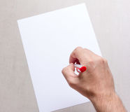 Male hand with a ballpoint pen and a blank white sheet of paper on grey background, top view closeup Stock Photography
