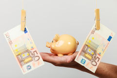 Male hand with banknote and piggybank Stock Photo