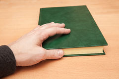 Male hand and book with empty dark green cover Stock Photography