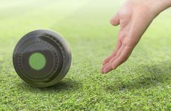 Hand And Lawn Bowl. A male hand bowling and releasing a blue wooden lawn bowling ball on a green lawn grass surface -3D render Stock Images