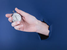 Male hand breaking through the blue paper background and holding antique clock Stock Photos