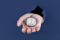 Male hand breaking through the blue paper background and holding antique clock Royalty Free Stock Photo