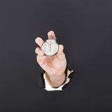 Male hand breaking through the paper background and holding antique clock. High resolution. Royalty Free Stock Images