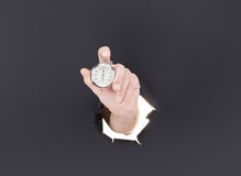 Male hand breaking through the paper background and holding antique clock. High resolution. Stock Photography
