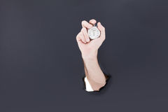 Male hand breaking through the paper background and holding antique clock. High resolution. Royalty Free Stock Photos