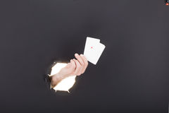 Male hand breaking through the paper background and holding bussiness card. High resolution. Royalty Free Stock Photo
