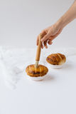Male Hand Brushing top of Pie with Milk on White Table Stock Images