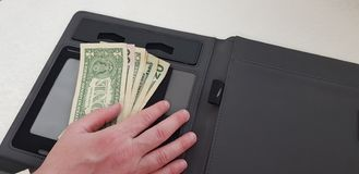 Male hand on bunch of dollar bills royalty free stock photo