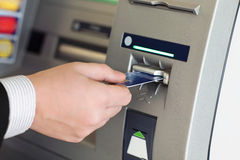 Male hand businessman inserts credit card into the ATM