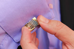 Male hand buttons cufflinks in purple shirt Stock Photo
