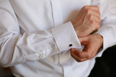 Male hand buttons cufflinks in white shirt. Royalty Free Stock Photo