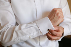 Male hand buttons cufflinks in white shirt. Royalty Free Stock Photography