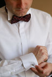 Male hand buttons cufflinks in white shirt. White spotted bow tie brown. Stock Photography