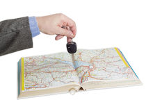 Male hand with car keys over an open road atlas. Male hand with car keys over an open old road atlas on a light background Stock Photography
