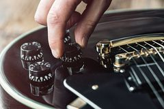 Male hand changing electric guitar settings. Tuning a timbre regulator royalty free stock photography