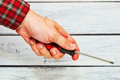 Male hand in checkered shirt holding a screwdriver Stock Images
