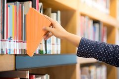 Male hand picking orange book in library. Male hand choosing and picking orange book in public library, education research and self learning in university life Stock Image
