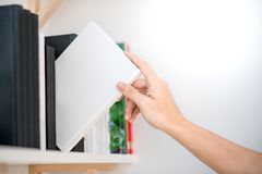 Male hand picking white book on bookshelf. Male hand choosing and picking white book on bookshelf in public library, education research and self learning in Royalty Free Stock Image
