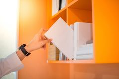 Male hand picking white book on bookshelf. Male hand choosing and picking white book on orange bookshelf in public library, education research and self learning Stock Images