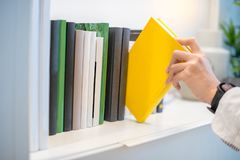 Male hand picking yellow book on white bookshelf. Male hand choosing and picking white book on white bookshelf in public library, education research and self Royalty Free Stock Photography