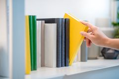 Male hand picking yellow book on white bookshelf. Male hand choosing and picking white book on white bookshelf in public library, education research and self Stock Images