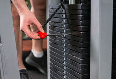 Male hand choosing a weight on a metal weights of bodybuilding e. Quipment in a gym Stock Images