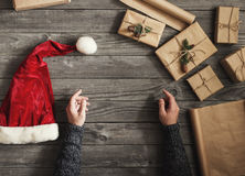 Male hand with christmas gifts and santa hat Stock Images