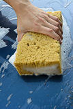 Male hand is cleaning  car bonnet with yellow sponge Stock Image