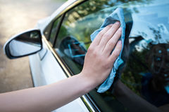 Male hand cleaning car window with microfiber cloth. Male hand cleaning car window with blue microfiber cloth royalty free stock images