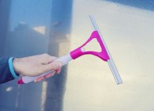 Male hand cleans glass window with Window Wiper Squeegee. Season Spring cleaning concept Stock Photos