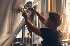 Male hand closes hatch of brewery tank Stock Photos