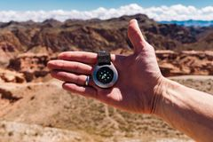 Male hand with compass on background of mountains in summer, point of view. Male hand with compass on background of mountains in summer, point of view Stock Photo