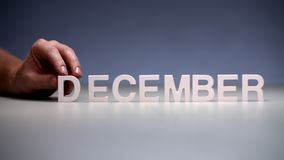 Male hand composition word december. Winter months on calendar and seasons year. Male hand composition word december on table background. Conceptual composition stock video
