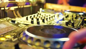 The male hand controls the DJ console. The room is illuminated with yellow light stock footage