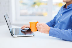 Male hand with cup of tea or coffee and laptop Stock Photos