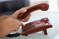 Male hand dial on landline phone Stock Image