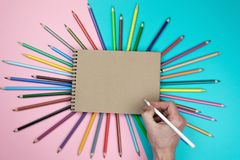 Male hand drawing, blank paper and colorful pencils. Branding stationery mockup scene, blank objects for placing your design. stock images