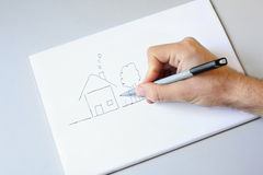 Male hand drawing house and garden on white paper royalty free stock images
