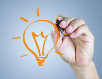Male hand drawing light bulb Royalty Free Stock Image