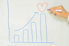 Male hand drawing love graph with increase arrow Stock Photo