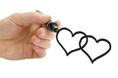 Male hand drawing two connected hearts on a virtual glass board. Stock Image