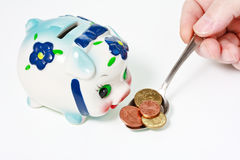 Male hand feeding a piggy bank with a coins Royalty Free Stock Photos