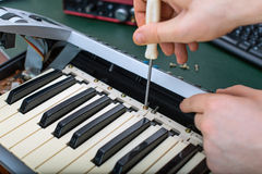 Male hand fixing midi keyboard. Royalty Free Stock Photo