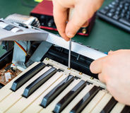 Male hand fixing midi keyboard. Royalty Free Stock Images