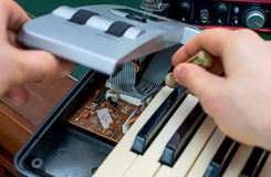 Male hand fixing midi keyboard. Stock Photography