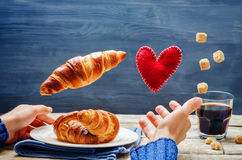 Male hand with flying croissant, toy heart and coffee Royalty Free Stock Images