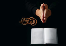 Male hand folded in prayer. Rosary beads closeup and koran on background Stock Image