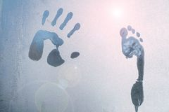 Male hand and foot print on frozen windows glass stock photos