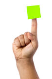 Male Hand Forefinger Blank Post-it Isolated. Blank green postit or post-it glued on top of forefinger of male hand isolated on white background Royalty Free Stock Images