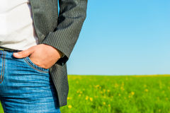 Male hand in the front pocket of jeans. On the background of nature Stock Photography
